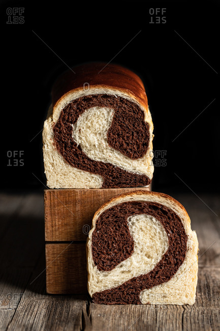 Delicious homemade bread with chocolate and banana flavor placed on wooden table in kitchen on black background