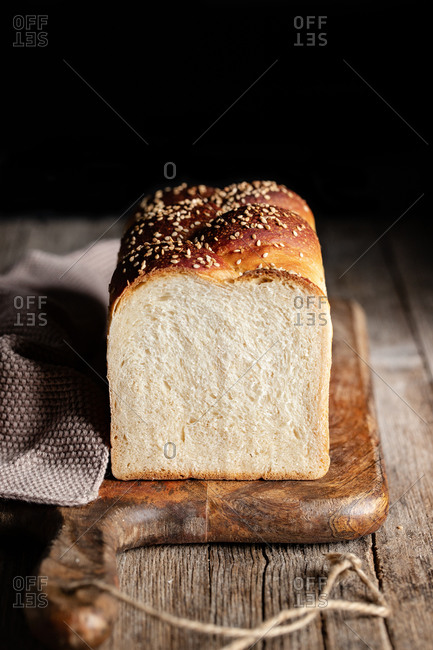 Loaf of fresh bread with sesame placed on cutting board in kitchen on black background