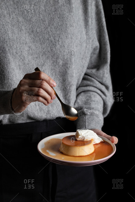 Unrecognizable female eating delicious caramel custard placed on plate with whipped cream on black background