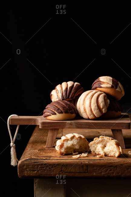 Freshly baked traditional concha bread placed on wooden cutting board on black background