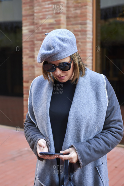 Serious female wearing trendy clothes with hat and sunglasses standing in city and browsing cellphone