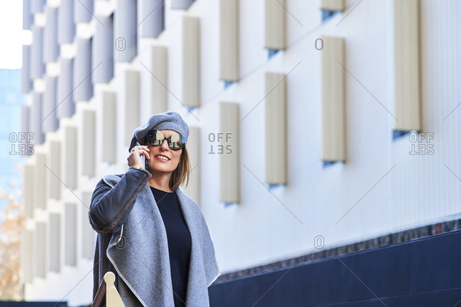 Front view of well dressed female entrepreneur standing along building and discussing business issues on smartphone while looking away with sunglasses and hat