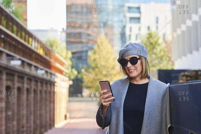 Happy female wearing trendy clothes with hat and sunglasses standing in city and browsing cellphone