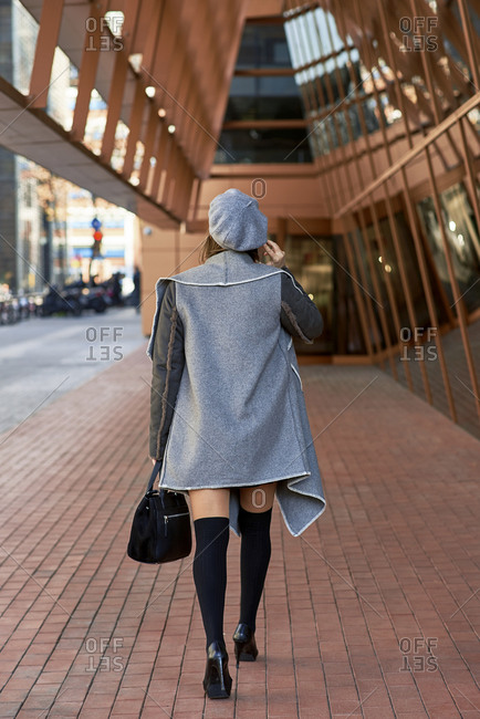 Back view of well dressed female entrepreneur walking along futuristic building and discussing business issues on smartphone