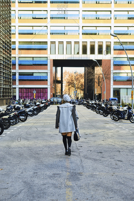 Back view of anonymous female in elegant clothing walking along concrete road with parked motorcycles