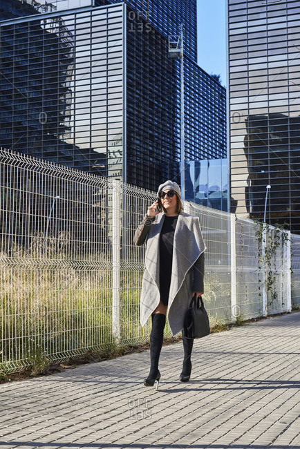 Side view of well dressed female entrepreneur standing along building and discussing business issues on smartphone while looking away with sunglasses and hat