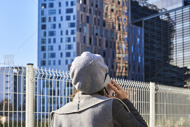 Back view of well dressed female entrepreneur standing along building and discussing business issues on smartphone with hat