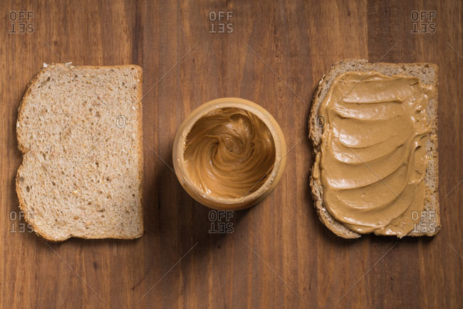 Top view of bread slices with creamy peanut butter placed on wooden table in kitchen with jar