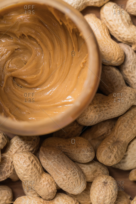 Top view of jar full of peanut butter placed on wooden table in kitchen with peanuts