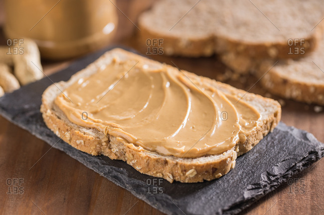 Top view of delicious piece of bread with peanut butter placed on black slate broad on wooden table with knife and fork