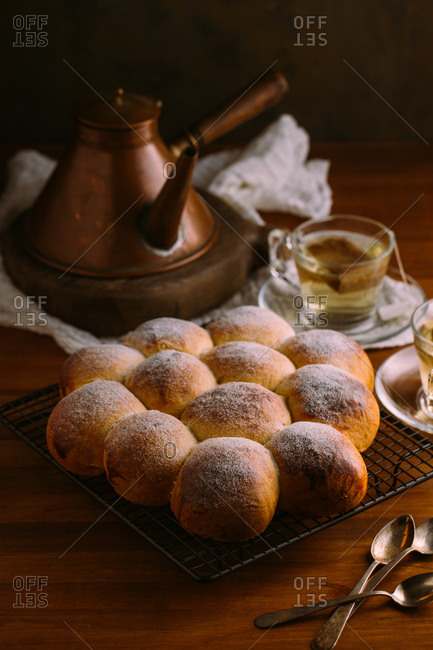 From above of identical appetizing buns with round shape and golden surface decorated with sugar powder on metal cooling rack on wooden table