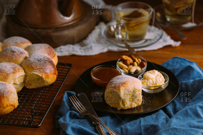From above of ceramic plate with fresh bun and small bowls with mix of nuts near jam and butter close to cup of green tea on crumpled towel