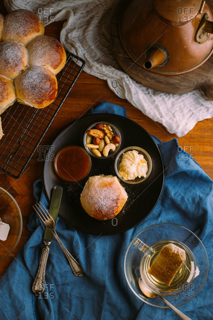 Top view of ceramic plate with fresh bun and small bowls with mix of nuts near jam and butter close to cup of green tea on crumpled towel