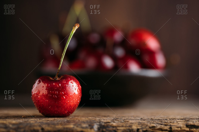 Close up view of cherry, on the background bowl full of fresh cherries on wooden table against dark background