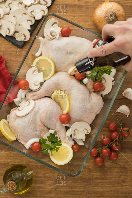Hand pouring beer over uncooked chicken with tomatoes lemon and mushrooms in glass oven recipient resting on a wooden table