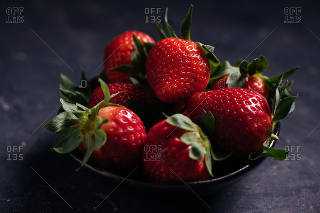 Closeup of delectable juicy ripe strawberries with green leaves arranged in black ceramic bowl on dark background