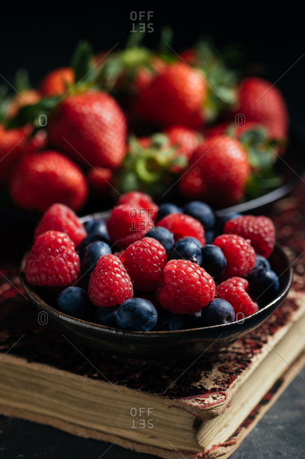 Composition with bowl with fresh ripe strawberries arranged near bowl with raspberries and blueberries on black surface