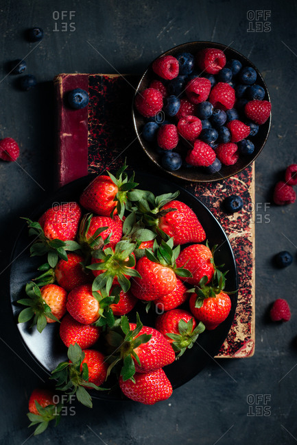 Top view composition with bowl with fresh ripe strawberries arranged near bowl with raspberries and blueberries on black surface
