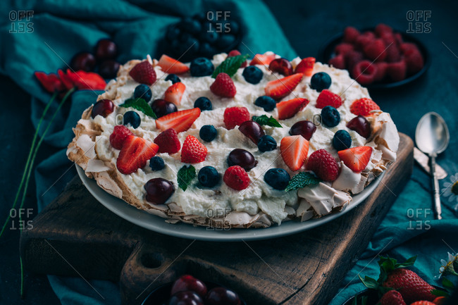 Delectable sweet meringue Pavlova cake with assorted fresh berries including strawberry and raspberry with cherry and blueberry served on table with berries and flowers