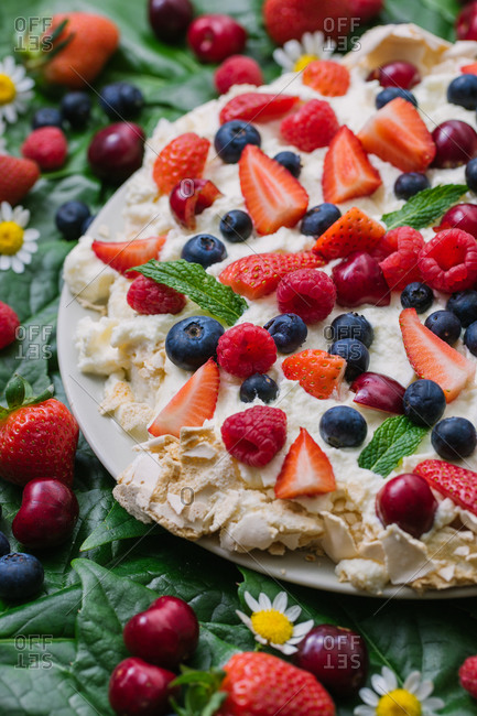 Plate with delicious summer dessert Pavlova cake with meringue and assorted fresh berries garnished with green leaves