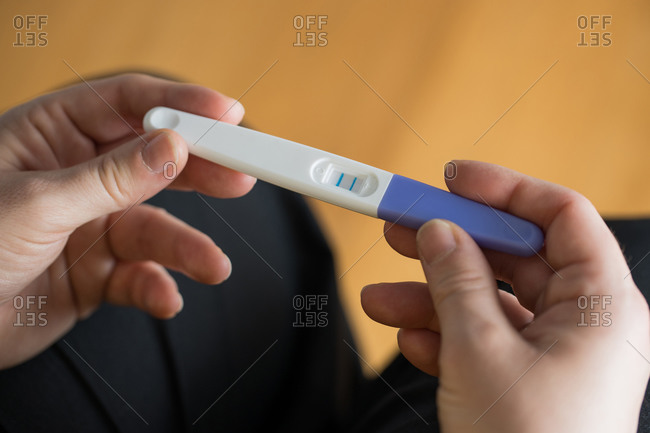 From above of crop unrecognizable female sitting holding pregnancy test with double bars