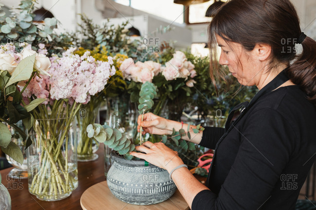 Side view of professional female florist arranging crassula succulent plants in ornamental ceramic pot while working in floristry studio