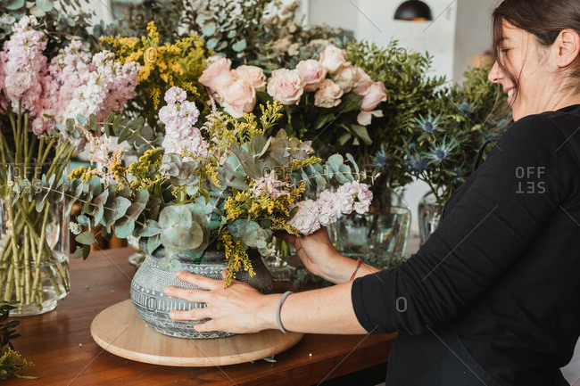 Side view of happy female designer arranging decorative blooming bouquets while working on order for event in creative floristry studio