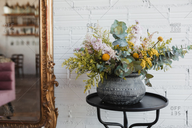 Beautiful bouquet with various flowers including goldenrod and craspedia flowers with green eucalyptus branches arranged in ornamental ceramic pot placed on small table against white brick wall with mirror in creative floristry studio