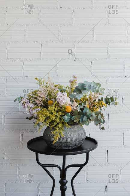 Beautiful bouquet with various flowers including goldenrod and craspedia flowers with green eucalyptus branches arranged in ornamental ceramic pot placed on small table against white brick wall in creative floristry studio