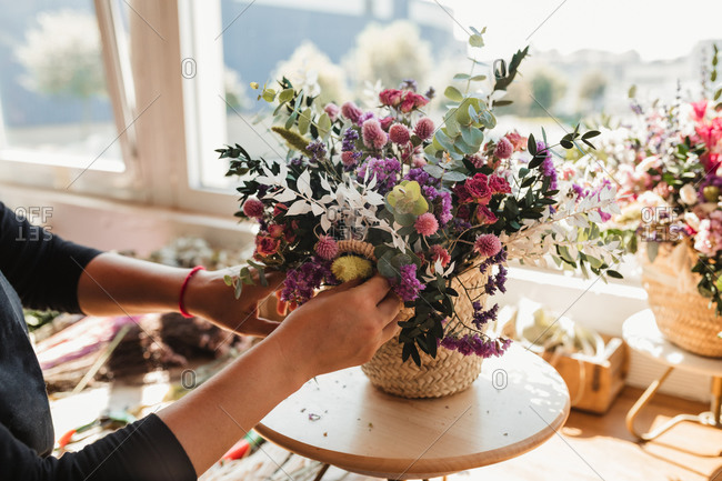 Crop of side view of female designer arranging decorative blooming bouquets while working on order for event in creative floristry studio