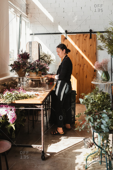 Side view of concentrated female designer arranging decorative blooming bouquets while working on order for event in creative floristry studio