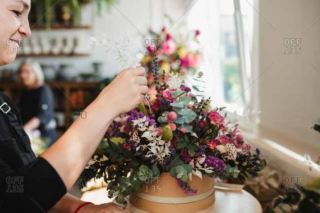 Crop of side view of concentrated female designer arranging decorative blooming bouquets while working on order for event in creative floristry studio