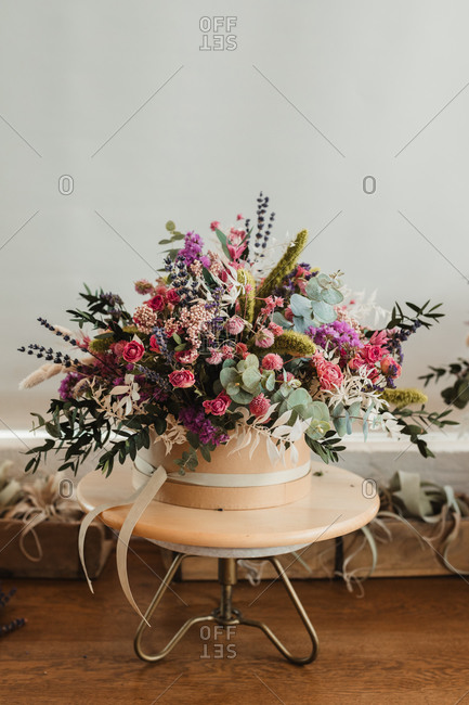 Beautiful bouquet with various flowers arranged in ornamental pot placed on small table against white wall in creative floristry studio