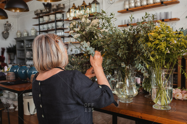 Back view of professional adult female florist choosing green decorative plants for composition while working in cozy floristry studio