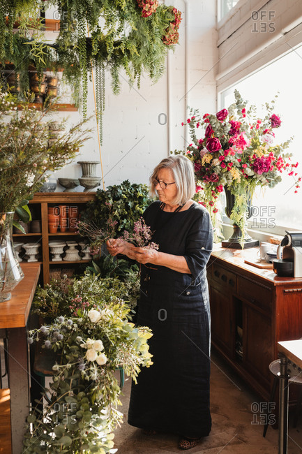 Professional adult female florist choosing green decorative plants for composition while working in cozy floristry studio