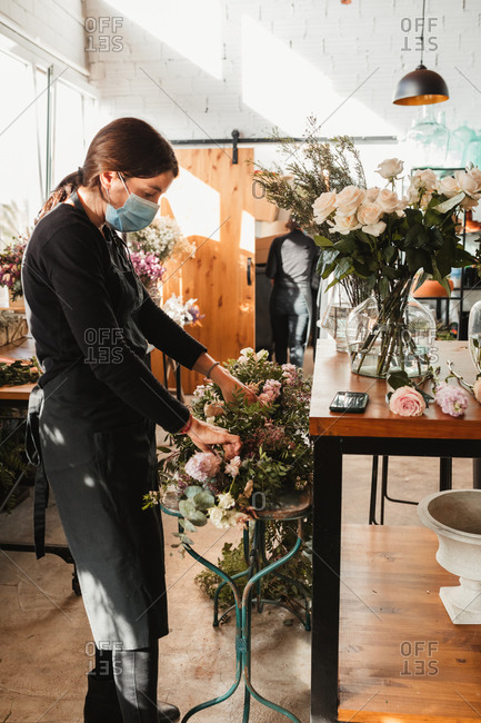 Side view of professional female floral master in protective mask arranging decorative composition with blooming roses while working in floristry workshop