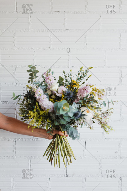 Crop anonymous female holding beautiful blooming bouquet of various fresh flowers and decorative plants against white brick wall