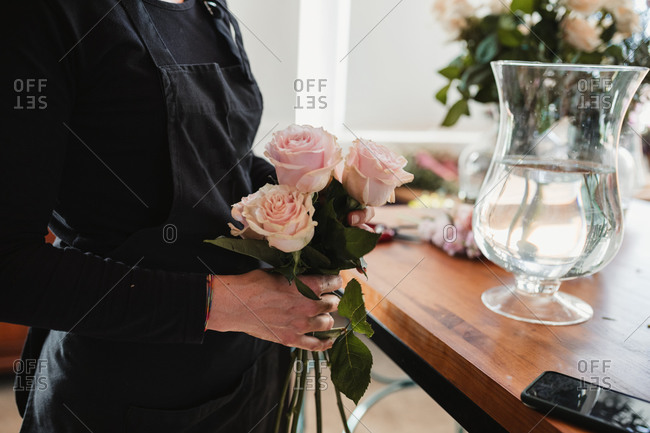 Side view of crop unrecognizable female florist holding beautiful gentle pink roses while standing at counter with glass vase filled with water during work in floristry salon