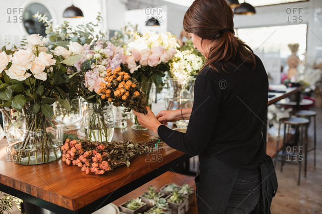 Side view of adult female floristry shop worker standing at wooden counter and arranging bouquets of fresh roses