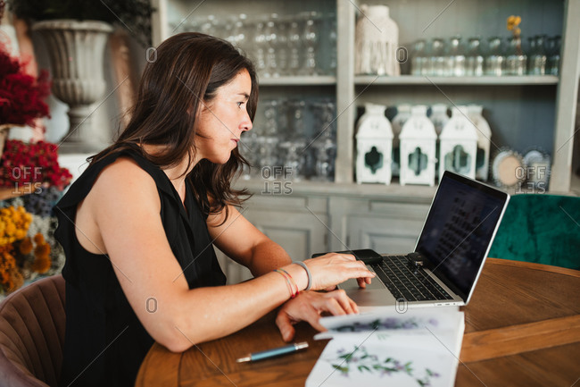 Side view of adult female owner of stylish floristry salon sitting at wooden table working with laptop near catalog of flowers