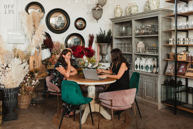 Side view of female owner of stylish floristry salon discussing details of order with customer while sitting together at table with laptop