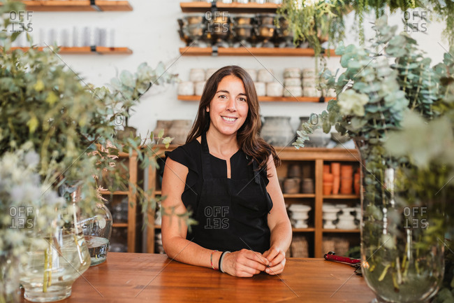 Positive successful female owner of floristry workshop looking at camera and smiling while standing at wooden counter among green decorative plants