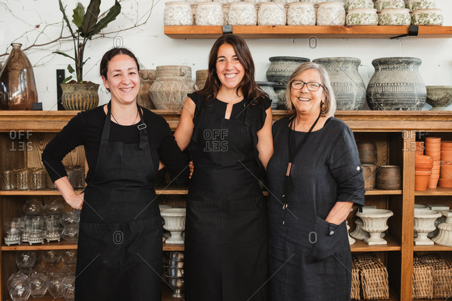 Positive professional female florists in black aprons smiling and looking at camera friendly while standing against shelves with various flower pots in stylish floristry shop