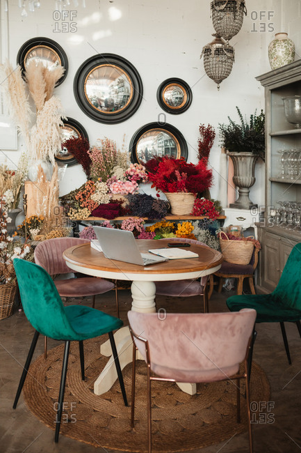 Cozy interior design of stylish floristry studio including round wooden table with colorful chairs and floral compositions placed near wall with decorative items