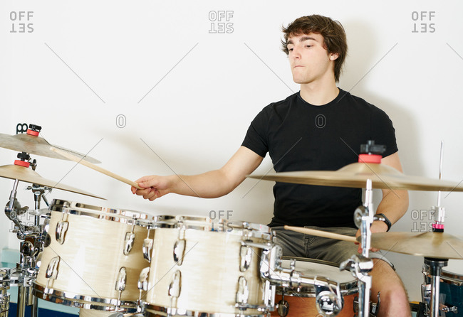 Calm casual focused male drummer playing on drum kit sitting on white background stage