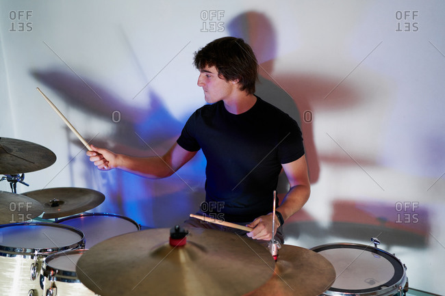 Calm casual male drummer playing on drum kit sitting on stage in shadows