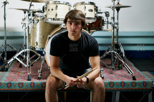 Young relaxed man with drumsticks sitting on stage with drum set and looking at camera