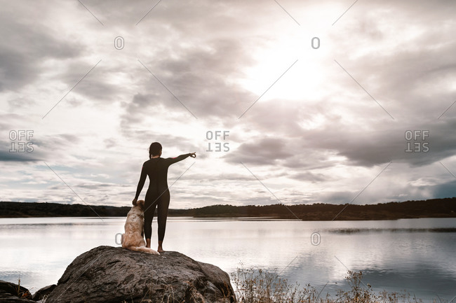 Back view of anonymous woman in black wetsuit standing with dog on stone and pointing away while observing lake nature