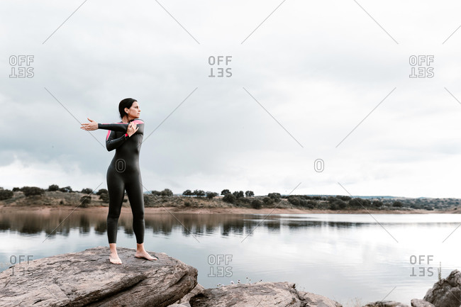 Full body slim barefoot female in black wetsuit warming up shoulder joints while stretching arms aside standing on peaceful shore of lake in overcast