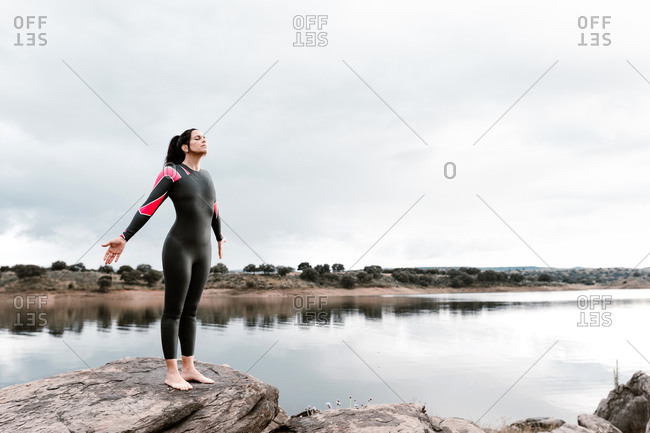Side view of barefoot female with eyes closed diver in wetsuit standing on boulder against peaceful lake in sunset light admiring landscapes